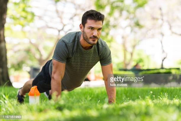 young man doing push-up exercises in the park - push ups stock pictures, royalty-free photos & images