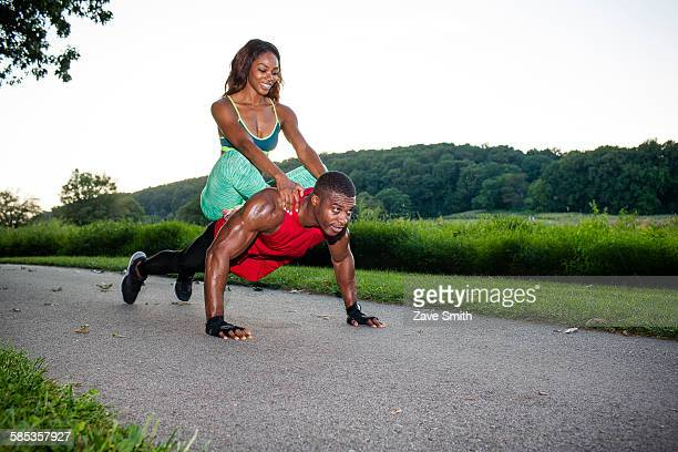 Young man doing pushups on rural road whilst giving girlfriend a piggyback