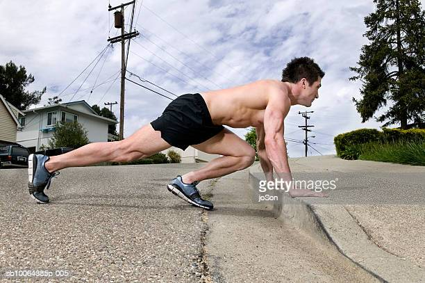 Young man doing push-ups on street, side view