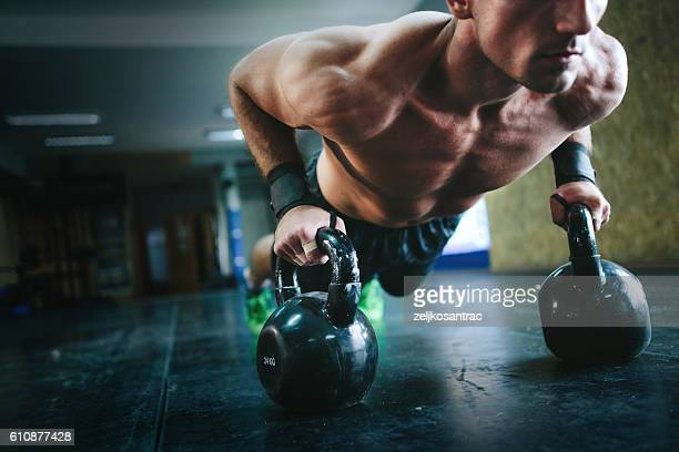 Young man doing pushups with kettle bells at the gym