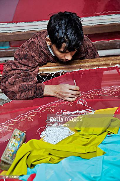 young man doing rich danka embroidery work on brightly colored fabric. thin polished golden shapes are secured using gold and silver wire. usually practiced by the men from the bohra community in udaipur. rajasthan, india. - indian bohra stock pictures, royalty-free photos & images
