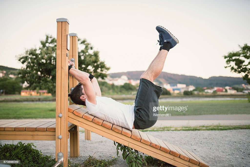 Young man doing sit-ups in a park, outdoors : Stock Photo