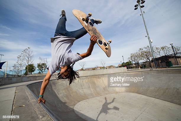 Young man doing skateboard trick upside down on edge of skateboard park