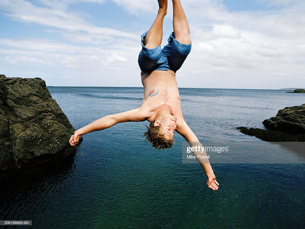 Young man doing somersault into water below : Stock Photo