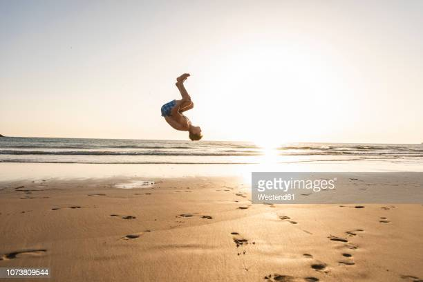 young man doing somersaults on the beach - somersault stock pictures, royalty-free photos & images