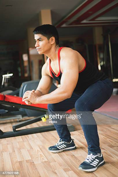 Joven haciendo squats en un gimnasio