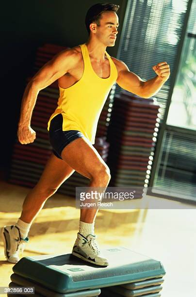 Young man doing step aerobics in sports hall
