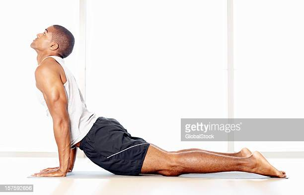 Young man doing stretches on a yoga mat against white