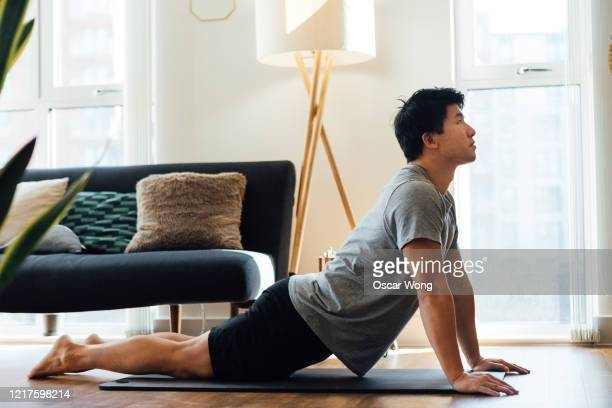 young man doing stretching exercise at home - confidence stock pictures, royalty-free photos & images