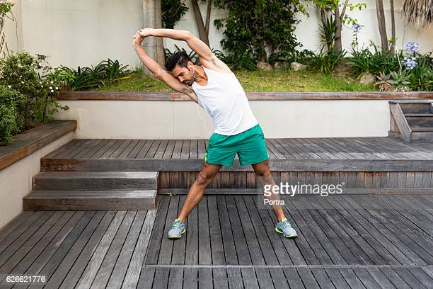 Young man doing stretching exercise in backyard