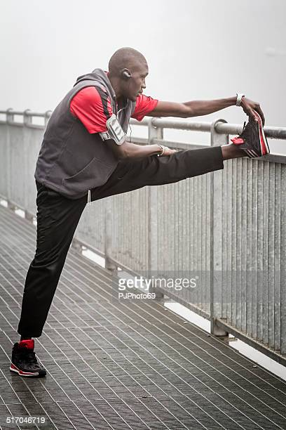 young man doing stretching in the fog on iron bridge - pjphoto69 stock pictures, royalty-free photos & images