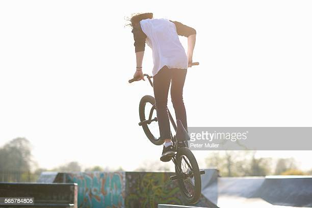 Young man doing stunt on bmx at skatepark, rear view