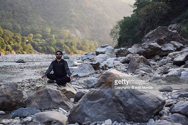 young man doing yoga exercises outdoors river bank of ganges - haridwar stock pictures, royalty-free photos & images
