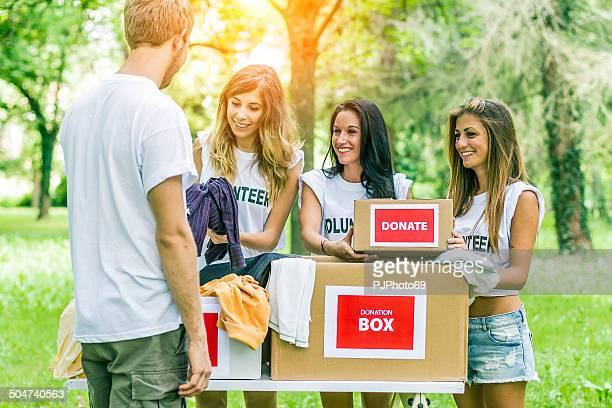 young man donates clothes to group of volunteers - pjphoto69 stockfoto's en -beelden