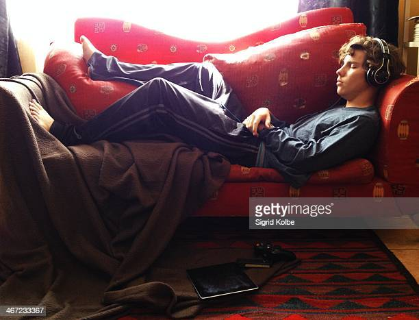 A young man dozing on a red couch listening to music