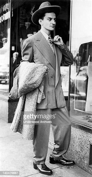 A young man dressed in a zootsuit checks out his image in a store front window Chicago Illinois 1943