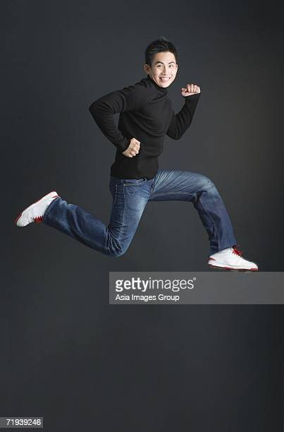 Young man dressed in black jumping and smiling at camera