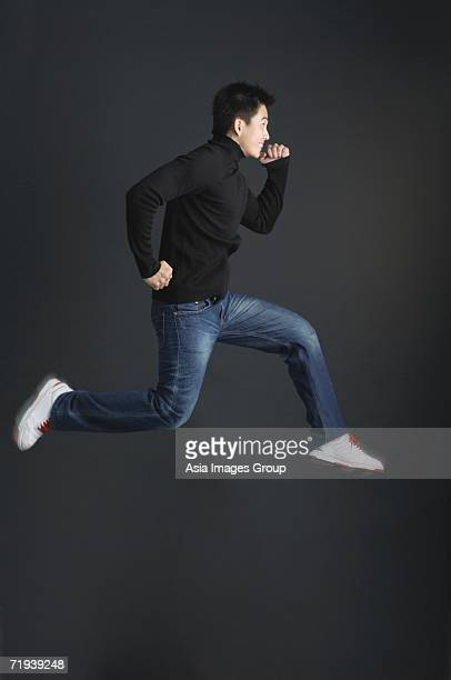 Young man dressed in black jumping in air