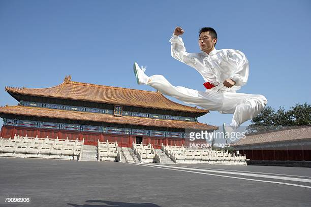 A young man dressed in kung fu silks, practices martial arts in front of an ancient Ming Dynasty-style Chinese temple.