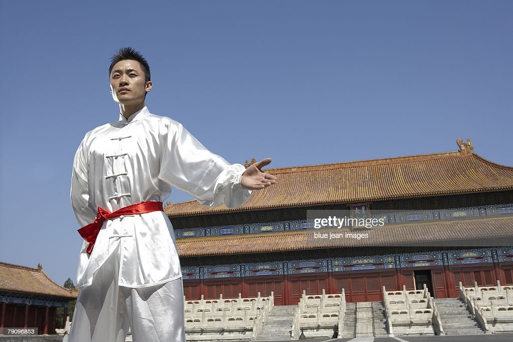A Young Man Dressed In Kung Fu Silks Stands In A Welcoming