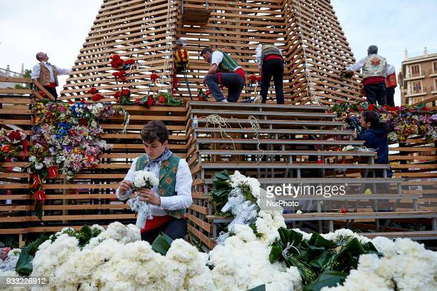 A young man dressed up in traditional costume works at the base of a large model of Saint Mary covered with flowers during Las Fallas Festival on...