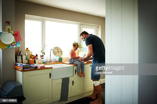 Young man dresses his little daughter