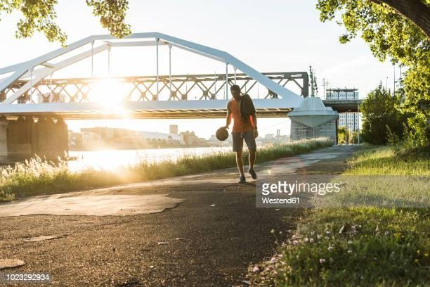 young man dribbling basketball at the river - mannheim stock-fotos und bilder