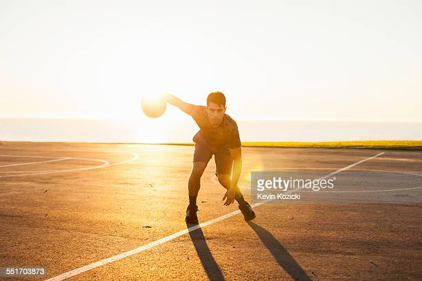 young man, dribbling basketball on court, outdoors - ドリブル ストックフォトと画像