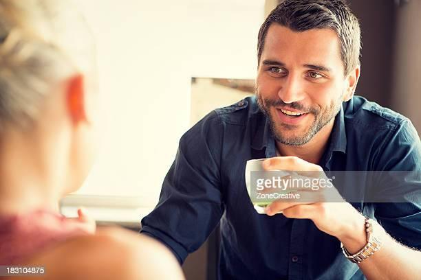 Young man drink a fruit juice at italian café