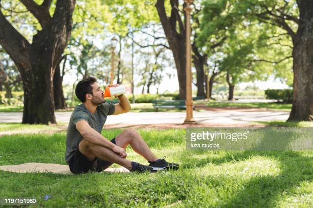 young man drinking a protein shake in the park - protein drink stock pictures, royalty-free photos & images
