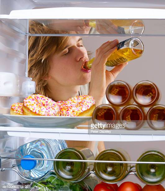 Young man drinking alcohol from fridge
