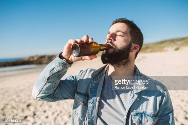 young man drinking alcoholic drink bottle while standing at beach during sunny day - trinken stock-fotos und bilder