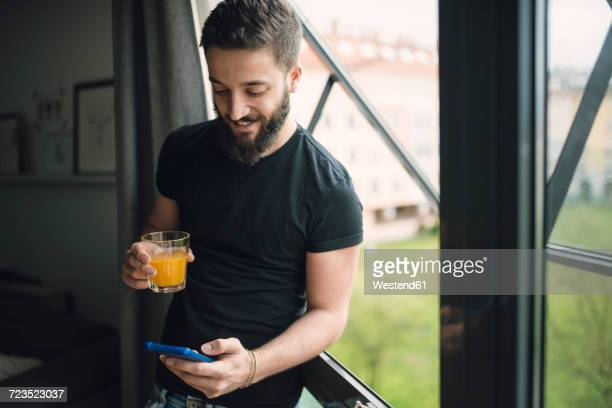 young man drinking an orange juice and using his smartphone at the window - t shirt preta imagens e fotografias de stock