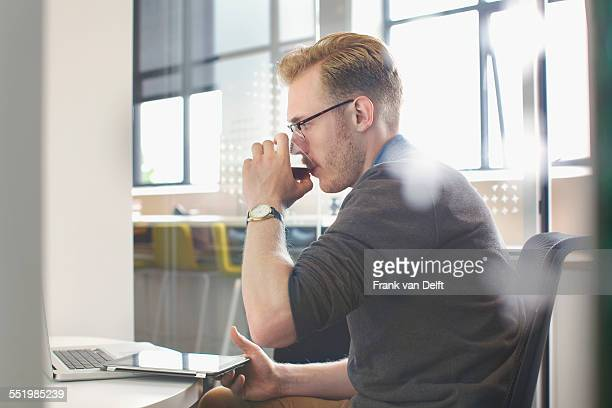 Young man drinking at office desk