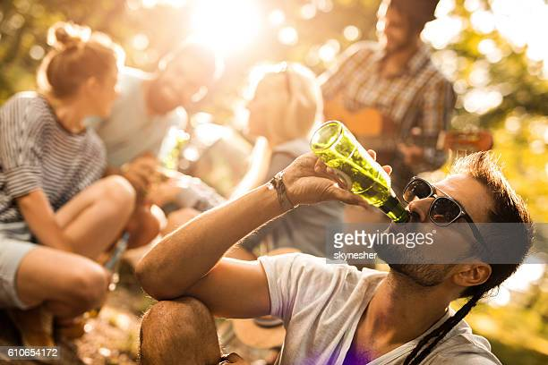 Young man drinking beer and enjoying in nature with friends.