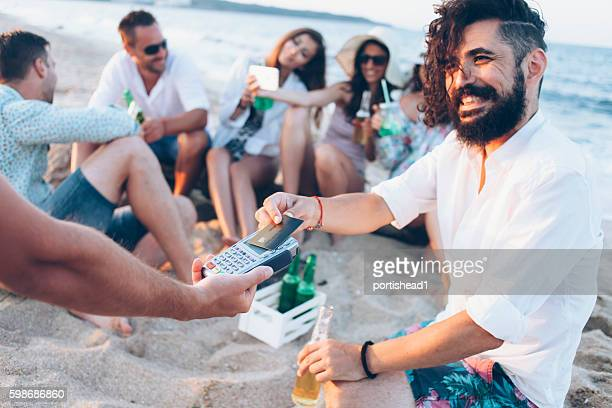 Young man drinking beer and using credit card on beach