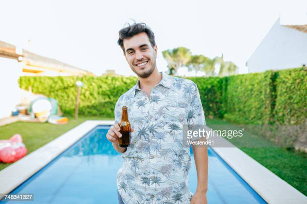 Young man drinking beer at the poolside