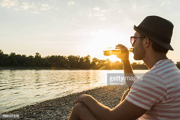 Young man drinking beer at the riverside at sunset