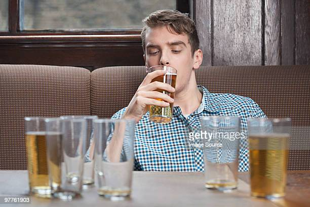 Young man drinking beer in bar
