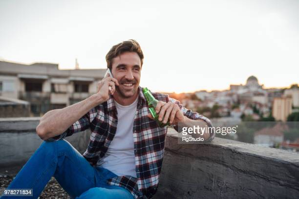 Young man drinking beer talking on a phone