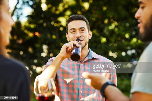 young man drinking beer while listening to friend - men friends beer outside stock pictures, royalty-free photos & images