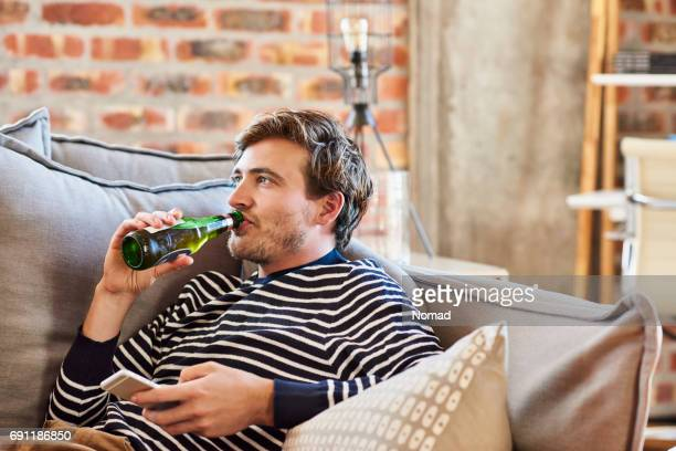 young man drinking beer while relaxing on sofa - beer alcohol stock pictures, royalty-free photos & images