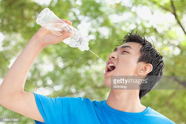 Young Man Drinking Bottled Water in Park
