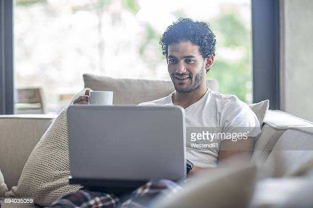 Young man drinking coffee and looking at laptop sitting on couch