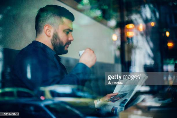 Young man drinking coffee and reading newspaper in the coffee bar