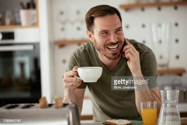 young man drinking coffee talking to