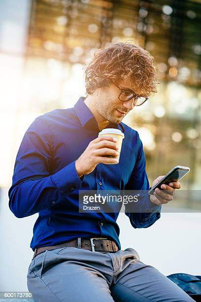Young man drinking coffee and using smartphone for mobile gaming