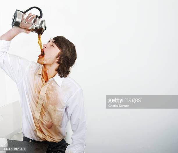 Young man drinking coffee from French press, coffee spilling on shirt