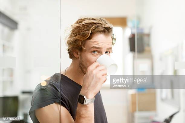 young man drinking coffee in office - tête composition photos et images de collection