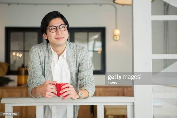 Young man drinking coffee in room